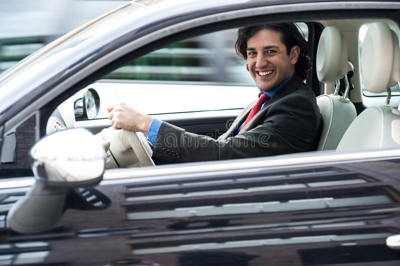 Corporate man driving his car. Young professional driving his new luxury car stock image