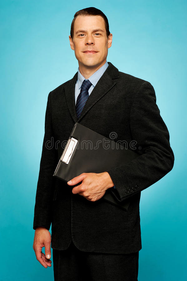 Corporate man holding clipboard and posing. Looking at camera stock image