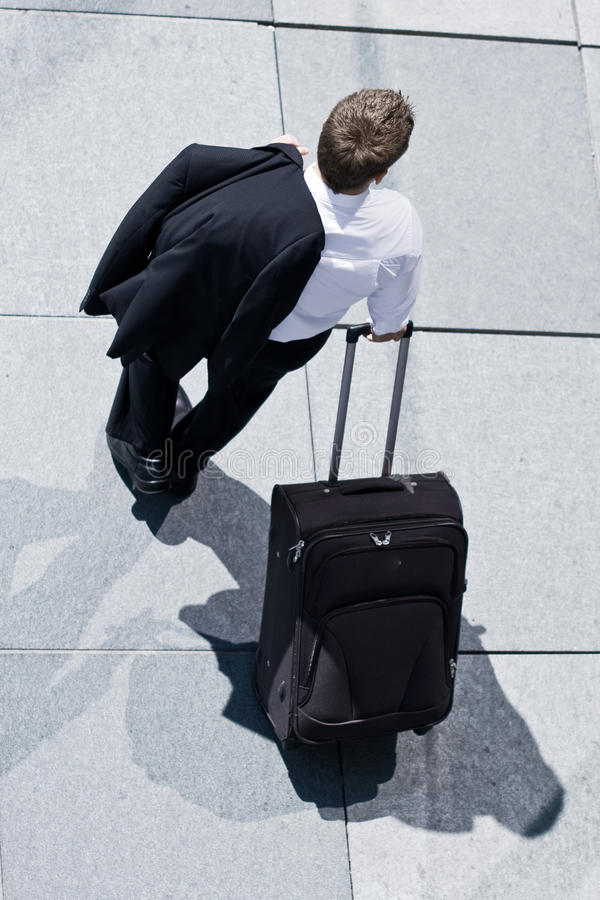 Corporate Man With Rolling Luggage Royalty Free Stock Photos