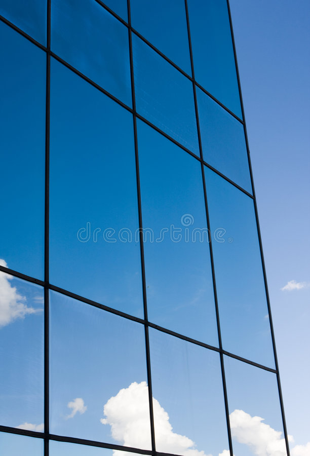 Corporate office. Exterior reflecting the blue sky and clouds above stock images