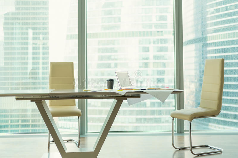 Corporate office interior with modern table, two chairs. Laptop, coffee cup, business drawings on table royalty free stock photography