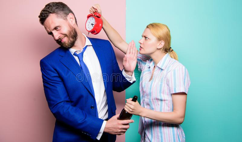 After corporate party. Man suffering from alcoholism. Angry wife meeting drunk husband late at home. Businessman with. Alcohol bottle and women with alarm clock royalty free stock photography