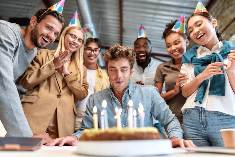 Corporate party. Young happy man blowing candles on cake while celebrating birthday with cheerful colleagues wearing royalty free stock photos