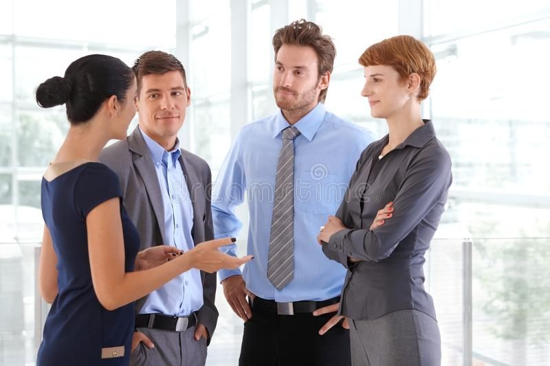 Corporate people chatting at business office lobby. Standing, gesturing, arms crossed, arms on hip, confident, wearing suit, confident royalty free stock images