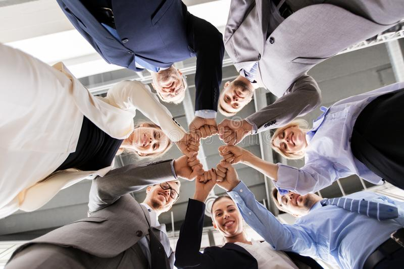 Happy business people making fist bump at office stock image
