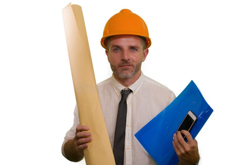 Corporate portrait of attractive and successful industrial engineer or contractor man in working hardhat holding blueprint royalty free stock photography
