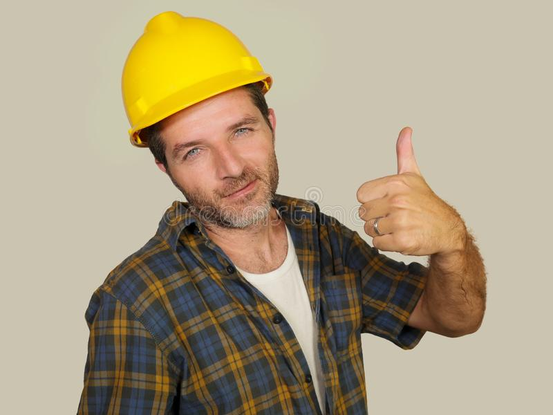 Corporate portrait of construction worker - Attractive and happy builder man in safety helmet giving thumb up smiling as royalty free stock image