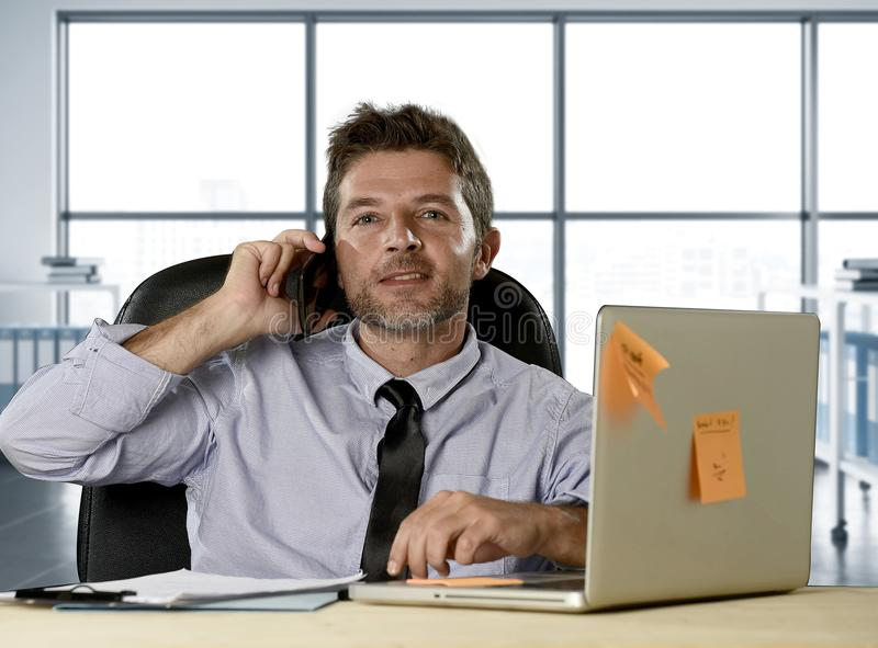 Corporate portrait of happy successful businessman in shirt and tie smiling at computer desk with mobile phone royalty free stock photography
