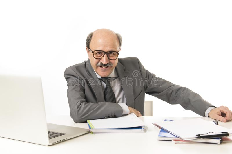 Corporate portrait of 60s bald happy business man smiling confident and satisfied sitting at computer laptop office desk working. With paperwork in job and royalty free stock images