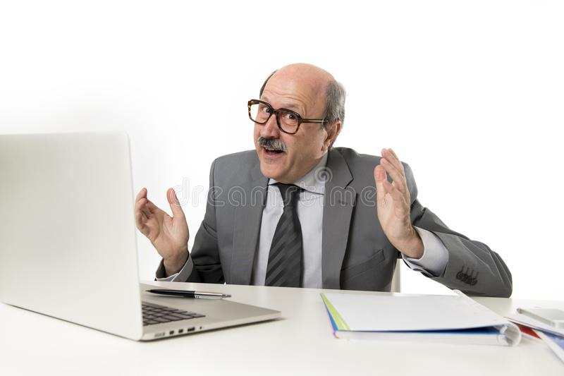 Corporate portrait of 60s bald happy business man smiling confid. Ent and satisfied sitting at computer laptop office desk working with paperwork in job and stock images