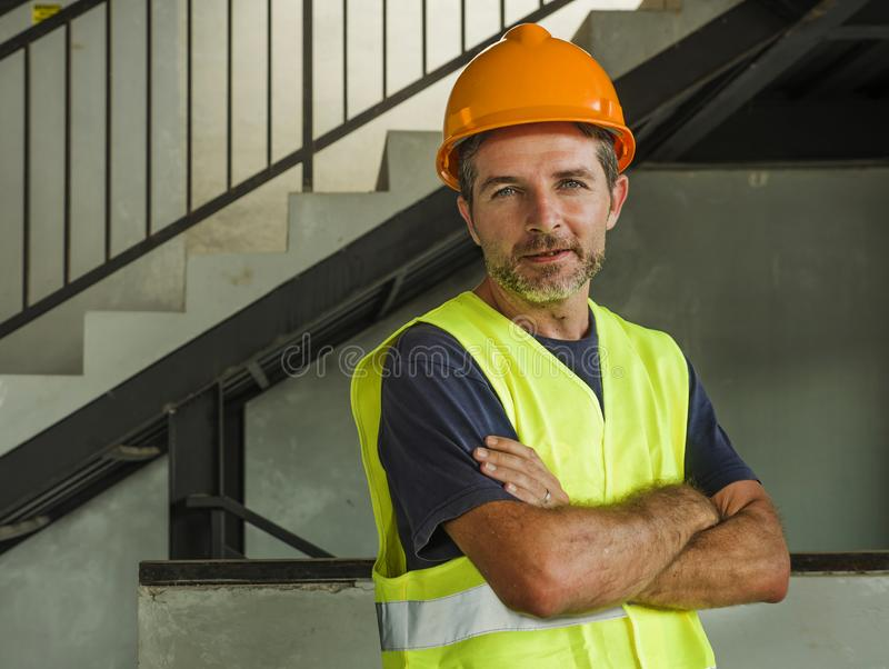 Corporate portrait of young attractive and happy builder man or constructor posing confident smiling wearing building helmet and royalty free stock photography