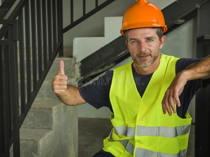 Corporate portrait of young attractive and happy builder man or constructor posing confident smiling wearing building helmet and stock image