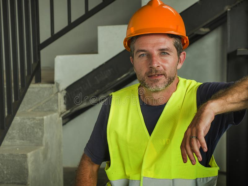 Corporate portrait of young attractive and happy builder man or constructor posing confident smiling wearing building helmet and stock photography