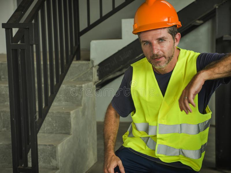 Corporate portrait of young attractive and happy builder man or constructor posing confident smiling wearing building helmet and royalty free stock photo