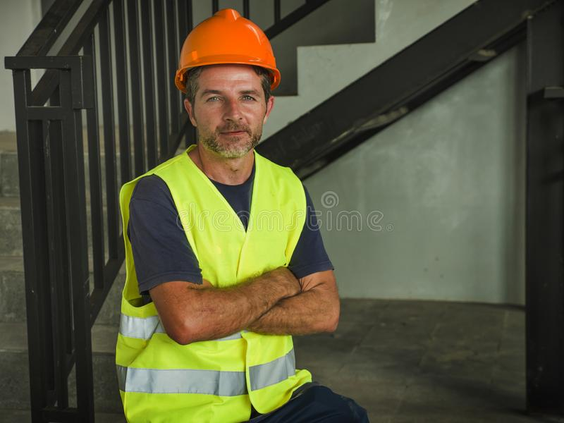 Corporate portrait of young attractive and happy builder man or constructor posing confident smiling wearing building helmet and royalty free stock photos