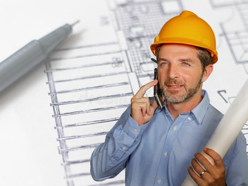 Corporate portrait of young attractive and happy industrial engineer man or architect in safety builder helmet talking on mobile stock images
