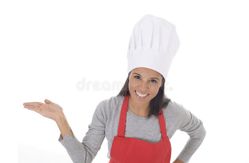 Corporate portrait of young attractive hispanic home cook woman in red apron posing happy and smiling isolated royalty free stock photo