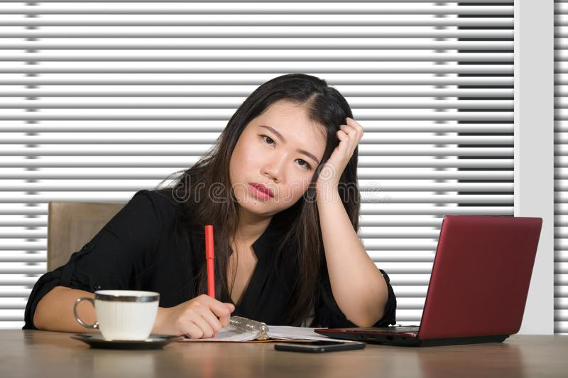 Corporate portrait of young attractive sad and stressed Asian Chinese woman working at company office computer desk feeling depres stock images
