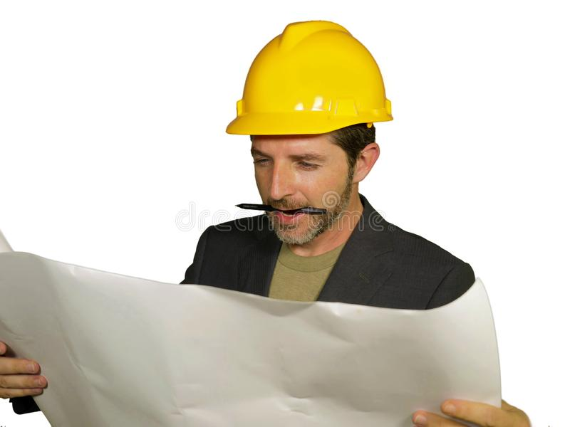 Corporate portrait of young attractive and successful industrial engineer or architect in safety builder helmet checking building royalty free stock photography