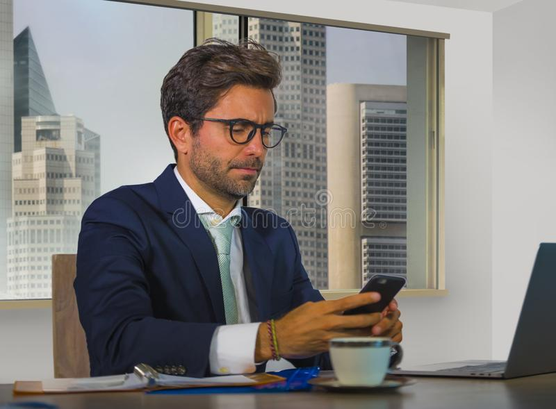 Corporate portrait of young happy handsome and attractive businessman working at computer desk in modern office at central busines royalty free stock photo