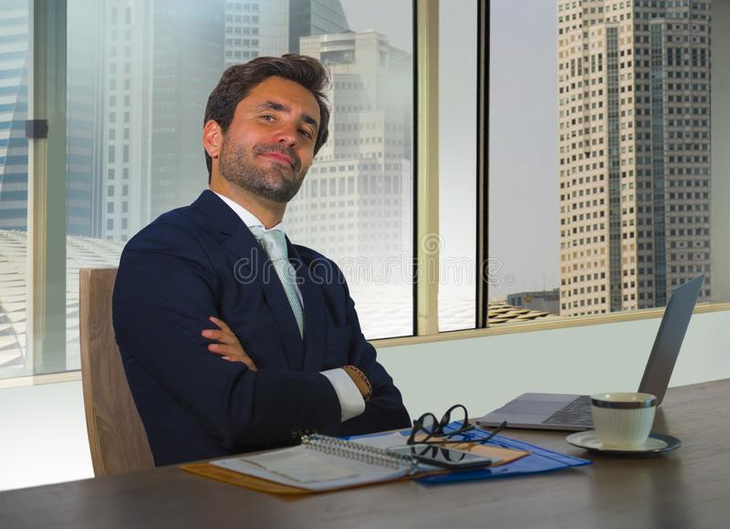Corporate portrait of young happy handsome and attractive businessman working at computer desk in modern office at central busines stock photo