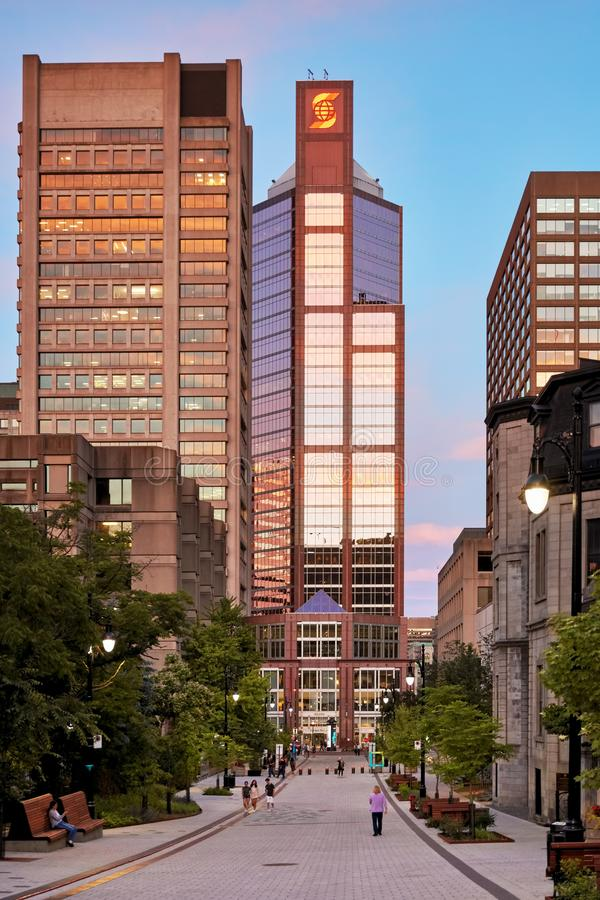 Corporate skyscraper buildings and people walking on McTavish street at sundown in Montreal, Canada royalty free stock photo