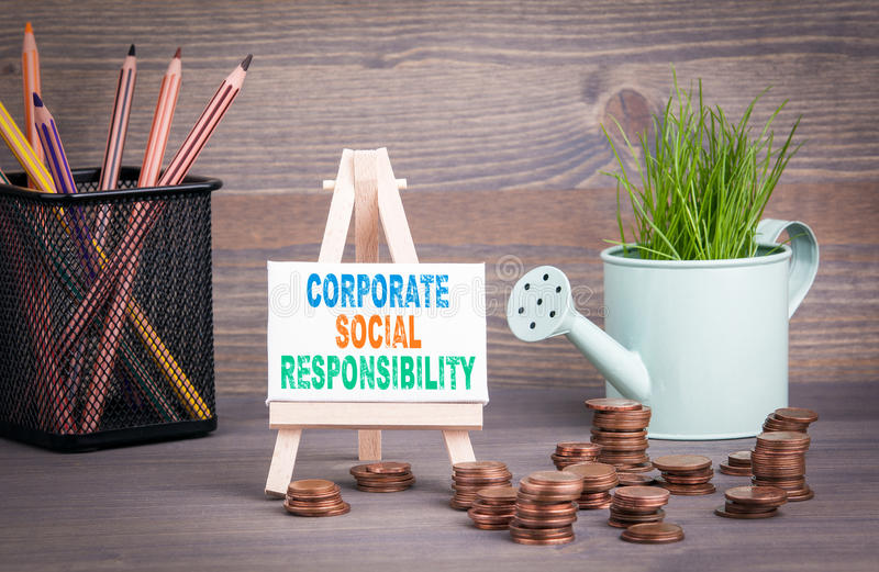 Corporate Social Responsibility Business Concept. Miniature watering pot with fresh green spring grass and small change royalty free stock photo