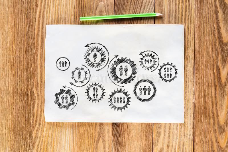 Corporate social responsibility concept. With group of rotating gears and cogs. Human resources cooperation sketch on wooden surface. Workplace with paper and royalty free stock photos