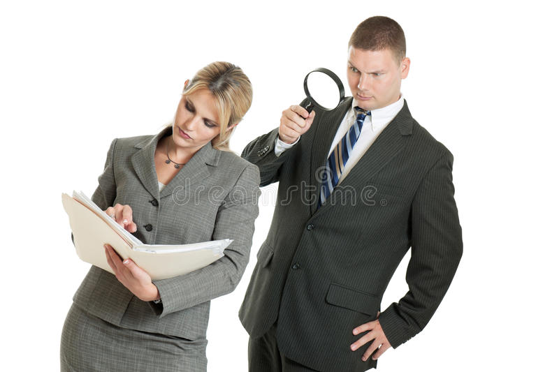 Corporate spying. A business men spying on a business women reading papers with magnifying glass isolated on white stock image
