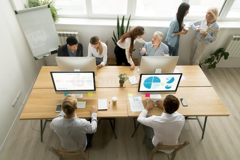 Corporate staff working in office together using computers and t. Corporate staff working talking in office together, diverse young and old coworkers using royalty free stock image