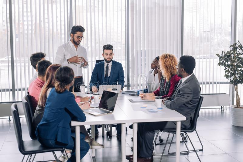 Corporate trainer teaching interns supervising brainstorming disscussion. Indian corporate trainer is teaching interns, while supervising brainstorming stock image