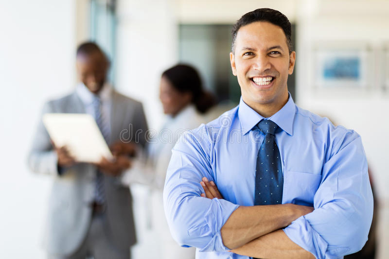 Corporate worker in modern office. Good looking corporate worker in modern office with colleagues on background royalty free stock photo