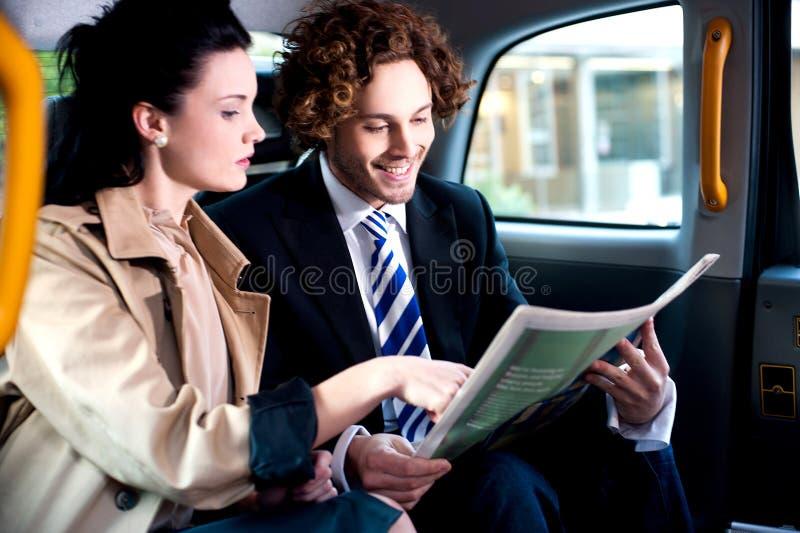 Corporates che discute le finanze pubblicate in giornale fotografia stock
