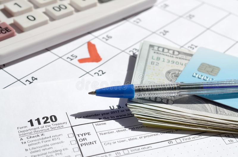 1120 Corporation Income Tax Return blank with dollar bills, calculator and pen on calendar page with marked 15th April. 1120 Corporation Income Tax Return blank stock photo