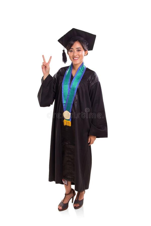 Corps de graduation de signe de paix de fille plein au-dessus du fond blanc image stock