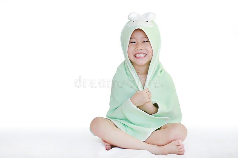 Corps de sourire de couverture de petite fille asiatique heureuse d'enfant sous la serviette après le bain se reposant sur le lit images stock