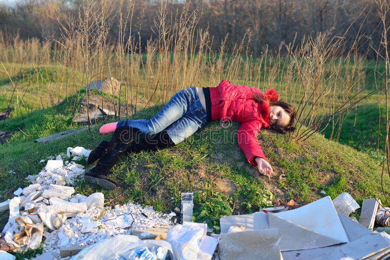 Corpse of a young girl lies on a landfill stock photography
