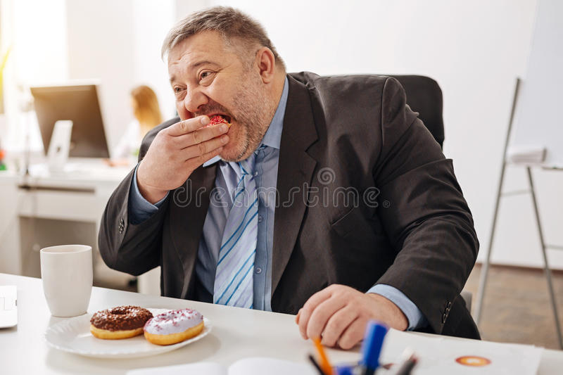 Corpulent hungry employee biting a piece of a doughnut royalty free stock images