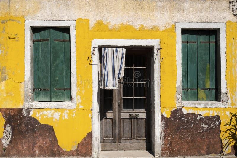 Corra abaixo da casa com descascamento da pintura amarela fotos de stock