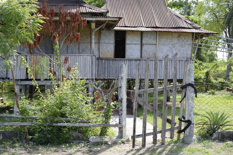 Corra abaixo da cerca de madeira descorada casa abandonada Rotting da exploração agrícola na praia foto de stock