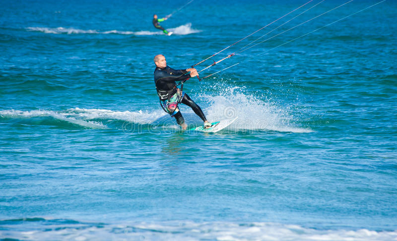 CORRALEJO, SPAIN - APRIL 28: Kitesurfer. Enjoys perfect wind and waves combination on 28 April 2012 in Corralejo, Fuerteventura, Spain royalty free stock images