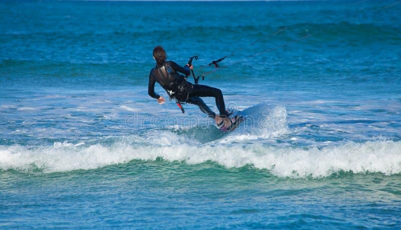 CORRALEJO, SPAIN - APRIL 28: Kitesurfer. Enjoys perfect wind and waves combination on 28 April 2012 in Corralejo, Fuerteventura, Spain royalty free stock photos