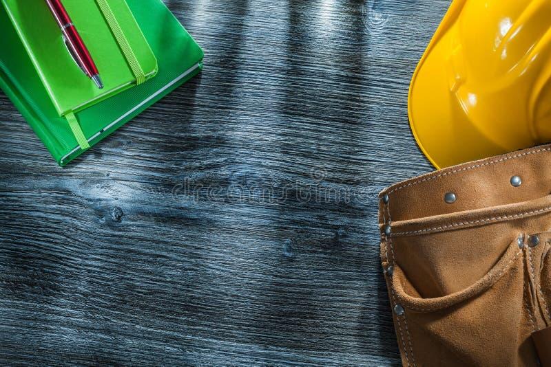 Correa de cuero de la herramienta del casco de la pluma de los cuadernos en el tablero de madera fotos de archivo