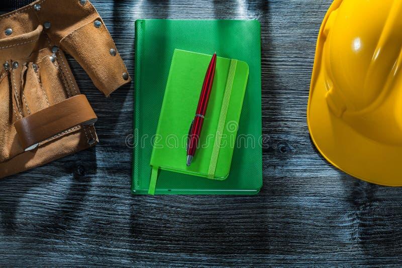 Correa de la herramienta del casco de la pluma de los cuadernos en el tablero de madera fotos de archivo libres de regalías