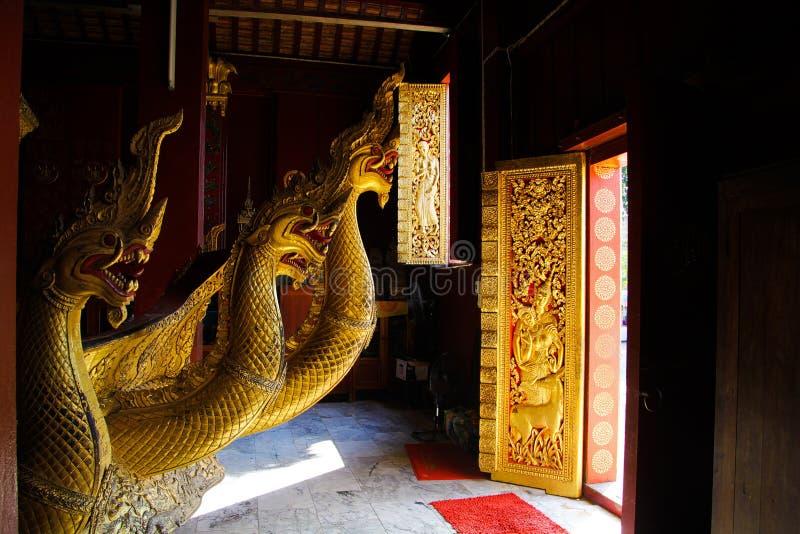 CORREA DE LUANG PRABANG WAT XIENG, LAOS - 17 DE DICIEMBRE 2017: Estatuas del dragón dentro del templo iluminado por luz del sol n foto de archivo
