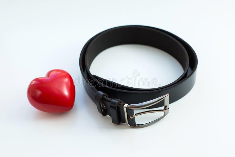 Correa negra y corazón rojo fotografía de archivo