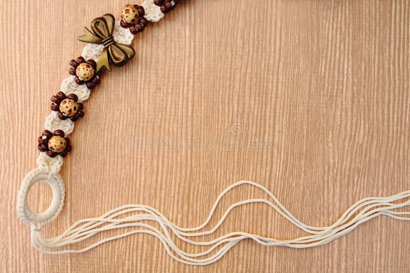 Correa tejida lanas en fondo de madera imagenes de archivo