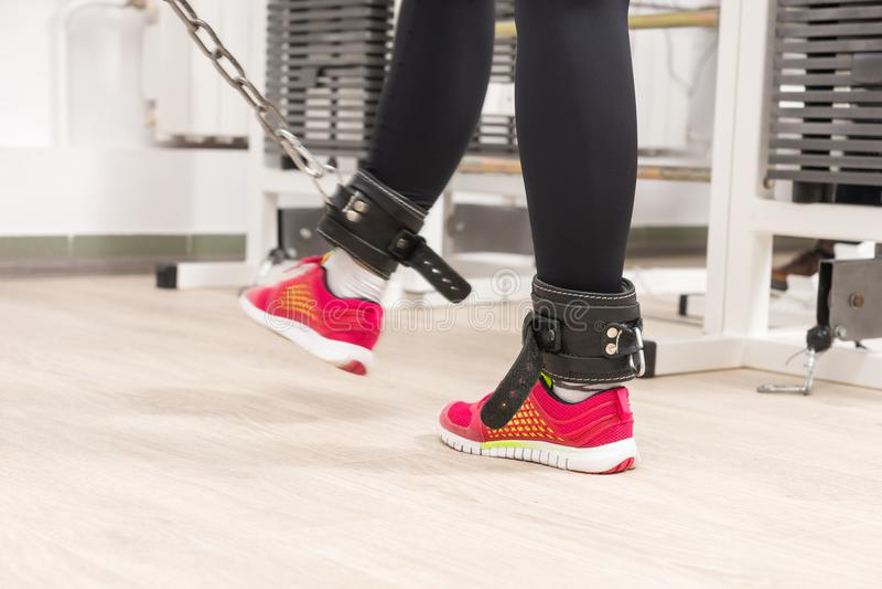 Correas de cuero del tobillo de la mujer que llevan en un gimnasio imagen de archivo