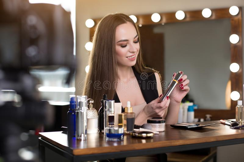Pleasant elegant young woman is recording video for her blog royalty free stock images