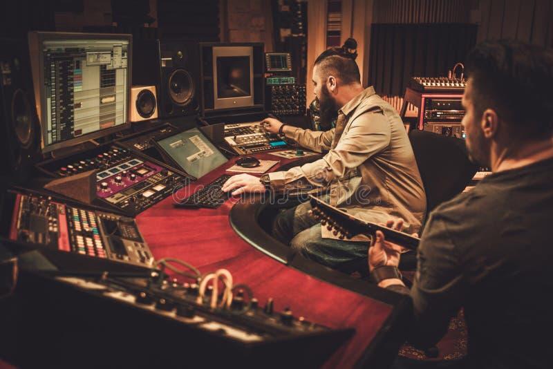 Correct ingenieur en gitaristopnamelied in de studio van de boutiqueopname royalty-vrije stock foto